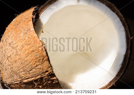 coconuts isolated on the black background Ripe half cut coconut on a wooden background. Ripe half cut coconut on a wooden background. Coconut cream and oil close up of a coconut on a wooden background