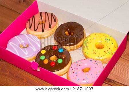 Six colored donuts in a pink box on a wooden background. Sweet donuts with glaze.