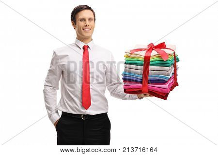 Formally dressed man with a stack of ironed and packed clothes wrapped with red ribbon as a present isolated on white background