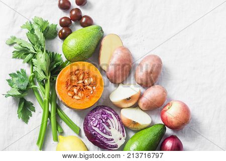 Vegetarian food set background. Pumpkin red cabbage avocado red onions kumato tomatoes celery apples potatoes beets on a light background top view. Healthy food. Flat lay
