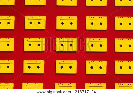 Collection Yellow Audio Cassettes Tapes On Red Background, Top View. Creative Concept Of Retro Technology