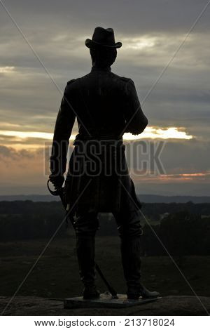 Gettysburg, Pennsylvania - September 9, 2009 - Vertical of a lightly silhouetted statue of a Civil War Officer with saber in hand overlooking the battlefields of Gettysburg Military Park, Pennsylvania a little before sunset on a cloudy day in September.