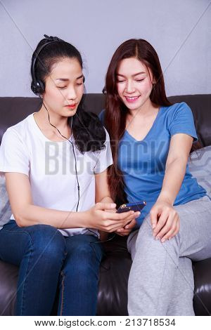 Two Woman Listening To Music In Headphones With Moblie On Sofa At Home