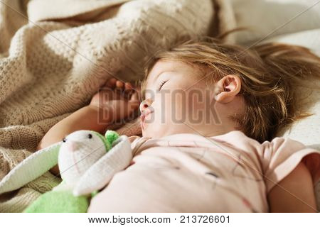 Sleeping Little Girl. Carefree Sleep Little Baby With A Soft Toy On The Bed.