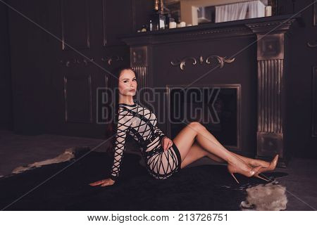 Vogue fashion style portrait of young beautiful elegant rich woman wearing evening dress and sitting on floor
