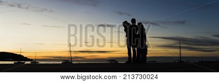Rear view of silhouetted family outdoors hugging looking at the sunset with the sea mountain and sailboats behind in a wide panoramic view against evening sky.