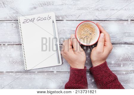 Notebook with goals for 2018 and male hand with cup of coffee. Planning and motivation for the new year concept. Top view.