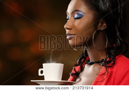 Close up face shot of attractive young african woman smelling coffee aroma with eyes closed.Low key portrait of elegant girl with cosmetic beauty make up.