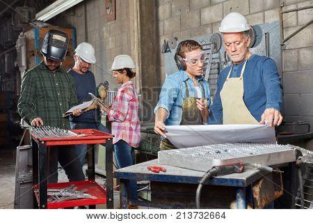 Metalworking workers planning in teamwork