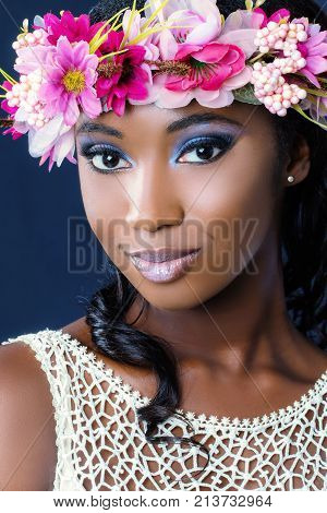 Close up beauty portrait of attractive young african bride wearing colorful flower garland.