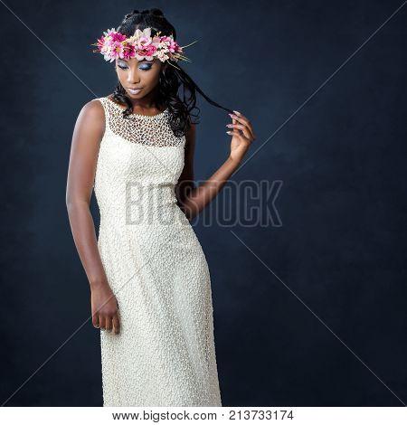 Close up studio portrait of elegant young african bride wearing colorful flower garland.Woman on white designer wedding dress against dark background.
