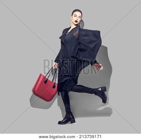 Fashion Model girl full length portrait on gray background. Beauty stylish brunette woman posing in fashionable clothes in studio. Winter fashion, black coat, trendy bag and shoes, Casual style.