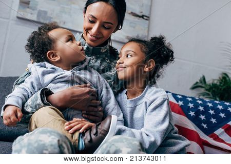 african american mother in military uniform sitting with her children american flag on background