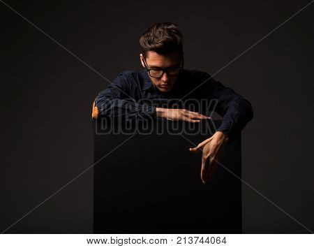 Young curious man portrait of a confident businessman showing presentation, pointing paper placard black background. Ideal for banners, registration forms, presentation, landings, presenting concept.