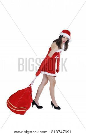Christmas concept : Beautiful young Asian woman in Santa Claus costume dragging Santa big red heavy bag isolated on white background
