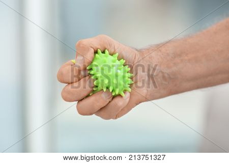 Hand of senior man doing exercise with rubber ball on blurred background