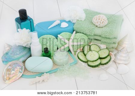 Skincare and body care beauty treatment with cucumber, bath salts, sponges, face cloths, aromatherapy essential oil, body lotion, bath foam, soap, carnation flowers and decorative shells.