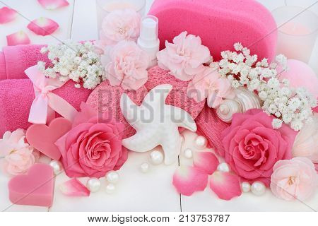 Beauty spa treatment and cleansing products with pink roses and carnation flowers, body lotion, starfish seashell soap, sponges, wash cloths with seashells and pearls on white wood background.