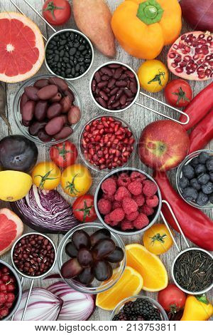 Super health food concept to promote healthy eating with fruit, vegetable, grain and pulses selection, high in antioxidants, anthocyanins, vitamins and minerals on rustic wood background.