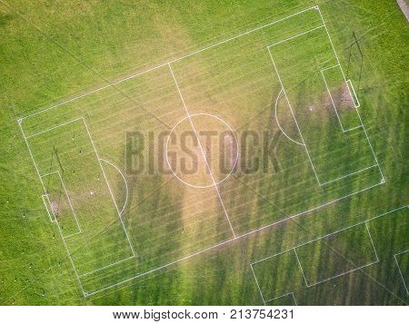Football (soccer) pitch, aerial view. Aerial drone photo looking down vertically onto an empty football (soccer) pitch with shadows cast by the low sun.