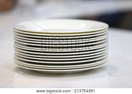 A stack of white plates.Plenty of plates. Plates from the restaurant. White plates. Plates for food
