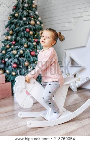 Happy Child Riding A Horse In The Room. Concept New Year, Merry Christmas, Holiday, Vacation, Winter