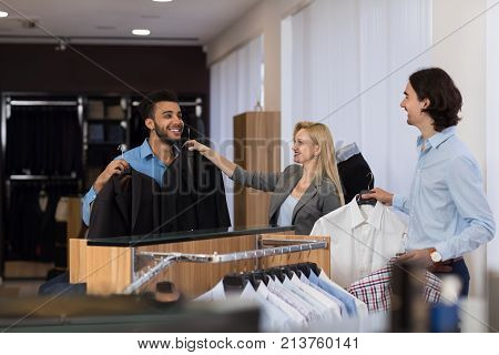 Female Shop Assistant Help Young Handsome Business Man Choose Suit In Clothes Shop, Two Businessmen In Luxury Male Clothing Store
