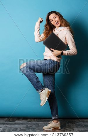 Full length portrait of a cheerful young girl holding laptop computer and celebrating success isolated over blue background