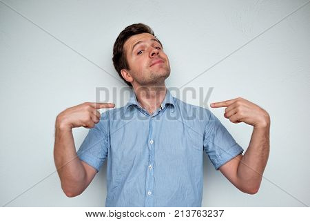 Self-satisfied and proud caucasian young man looks forward showing with index fingers on himself