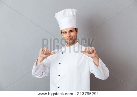 Picture of handsome young cook in uniform standing isolated over grey wall background. Looking camera pointing to himself.