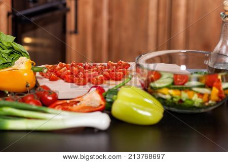 Ingredients of a vegetable salad on the kitchen table - with tomato slices on cutting board