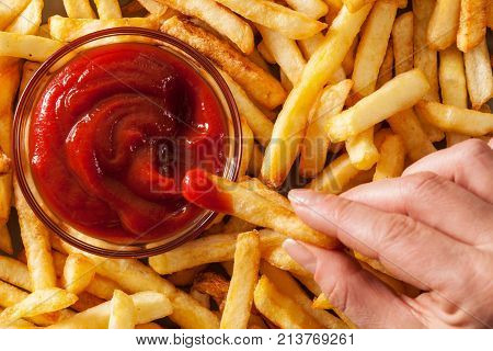 Hand dipping french fries in tomato sauce or ketchup - top view closeup