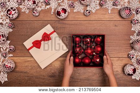 Child opening christmas present with red baubles inside seasonal decorations frame - closeup on hands