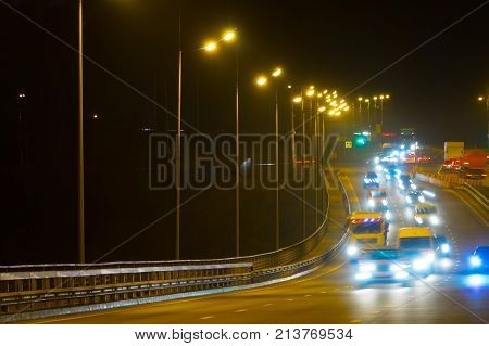 Highway Traffic Cars At Night Blured. Cars Moving On Road On Bridge Evening Blurry.