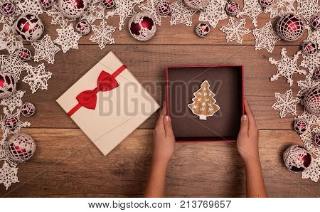 Hands presenting a christmas gift box - with gingerbread cookie pine tree inside top view