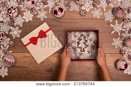 Hands giving or receiving christmas present a pine tree drawing in a gift box - in seasonal decorations frame