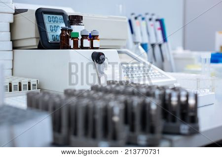 Lab atmosphere. Medical appliance with vials standing on the top focused  while other medical apparatuses surrounding it and ready for work