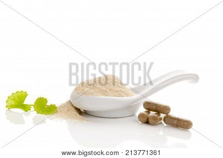 Gotu kola leaves capsules and powder in spoon. Isolated on white background. Centella asiatica Asiatic pennywort. Nutritional supplement natural remedy.