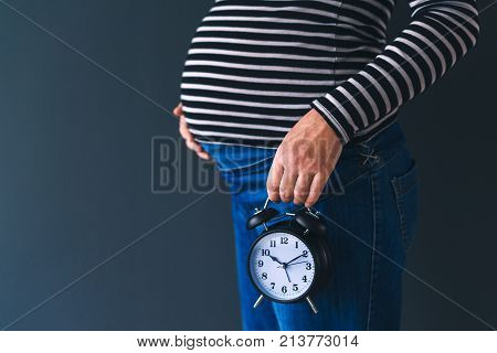 Pregnant female with vintage alarm clock expecting baby in third trimester of pregnancy