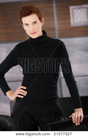 Portrait of trendy young businesswoman standing in office, looking at camera.?