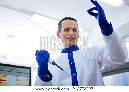 Perfect level. Experienced  appealing medical worker evaluating the level of liquid in the small glassware holding pipette while wearing labcoat