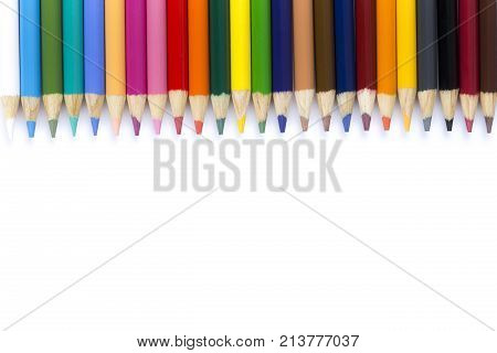Many colored pencils on isolation. Pencils on white background next to each other. Multicolored pencils a roll of a sheet of paper