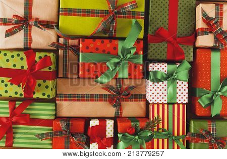 Packaging modern christmas presents. Lots of gift boxes in stylish wrapping paper, decorated with red, green satin ribbon bows. Christmas and winter holidays concept. Top view, flat lay