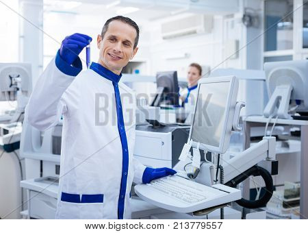 Successful experiment. Happy pleased male researcher achieving necessary reaction while placing his hand on the keyboard and brining up  glassware while standing in the lab