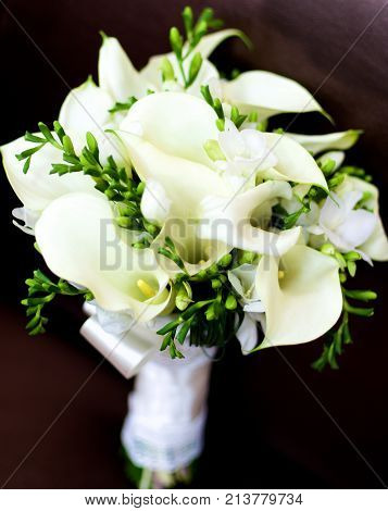 Beautiful Bridal Bouquet with Callas Snowdrops and Green Buds and Satin Ribbon closeup on Dark background. Focus on Pestle of Calla