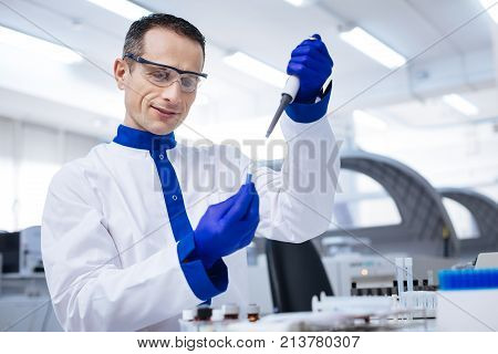 Great sample. Waist up of tranquil enthusiastic male lab assistant  who taking sample from the glassware with blue chemical placed there when standing on the blurred background