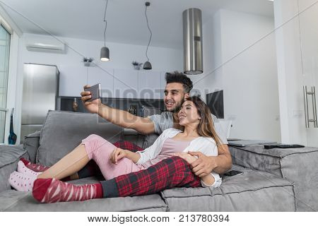 Happy Smiling Couple Taking Selfie Photo On Cell Smart Phones Sitting On Couch In Modern Apartment, Young Man And Woman Mke Self Portrait Embracing