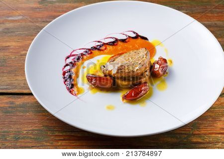 Roasted goose liver with date, apple and fruit and berry sauce painting close up. Creative french cuisine, delicatessen restaurant meal