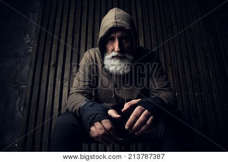 Serious bearded man ready to fight. Sport and fit man in hood sit on a chair. Workout and box sport. Extreme sport for old man. Close up portrait of man hands over his sports bandages