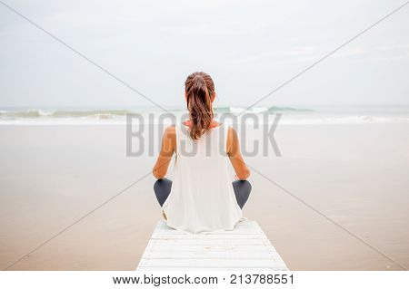 Woman Practices Yoga At The Seashore On Overcast Day